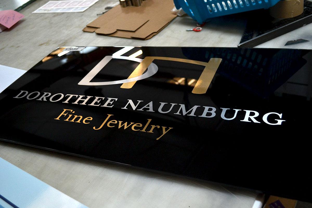 Black acrylic sign with metallic vinyl letters
